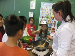 Th Awesome Rainbow Stir Fry team carefully adding ingredients into the wok!